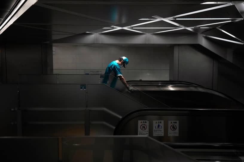 Токио. Работник метрополитена дезинфицирует поручни эскалатора
