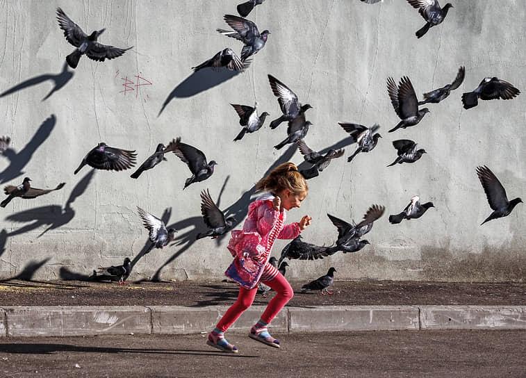 Санкт-Петербург. Девочка на фоне стаи голубей