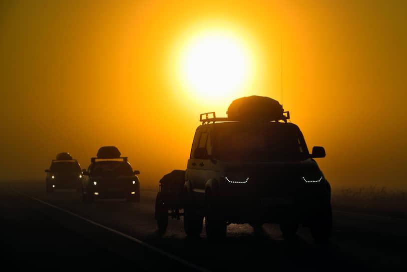 Новосибирская область, Россия. Автомобили на дороге во время туманного рассвета