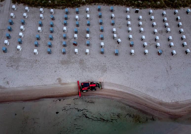 Шарбойц, Германия. Трактор очищает пляж Балтийского моря от грязи и водорослей