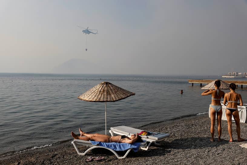 Мармарис, Турция. Туристы наблюдают как пожарный вертолет набирает воду