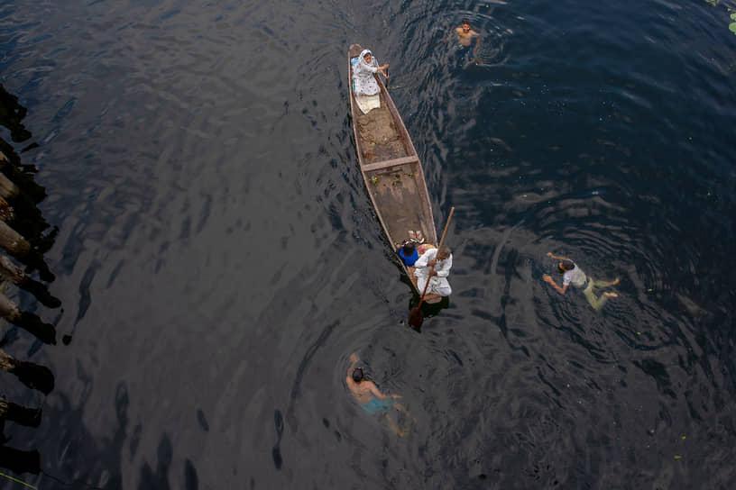 Сринагар, Индия. Кашмирская семья в лодке на озере