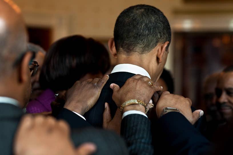 «Политика тогда становится лучше, когда мы соблюдаем правила приличия, а не культивируем в себе страх. Политика тогда становится лучше, когда мы не демонизируем друг друга, когда мы говорим о проблемах и ценностях, принципах и фактах, а не пытаемся уколоть и переложить вину на кого-либо» <br>В 2012 году Барак Обама вновь переизбрался, опередив республиканца Митта Ромни на 3,9% <br>На фото: с представителями духовенства во время молитвы