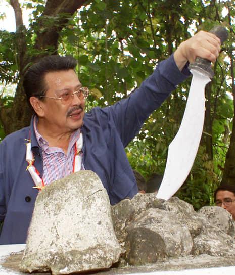 Президент Филиппин Джозеф Эстрада сжимает меч, запечатанный в куске скалы на историческом месте в городе Сан-Мигель. На этом месте находилась штаб-квартира филиппинских революционеров, которые сражались против испанцев в конце XIX века, 2001 год