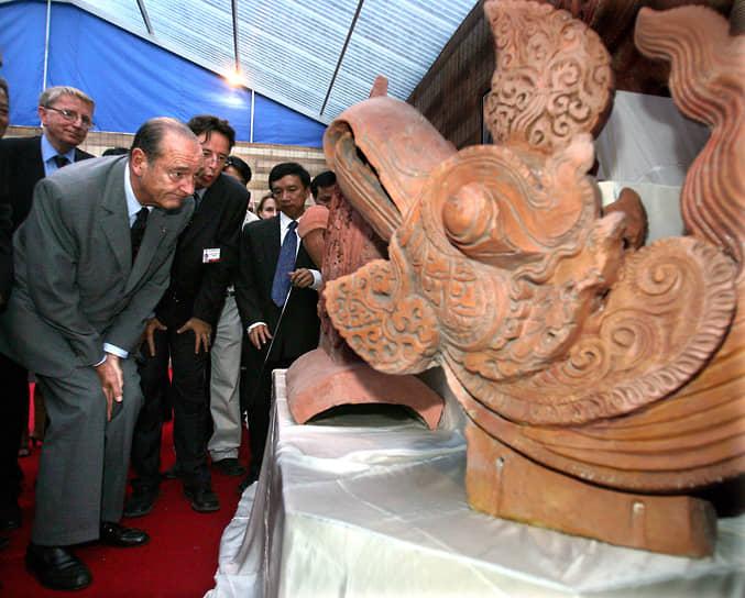 Президент Франции Жак Ширак осматривает голову Феникса во время посещения археологических раскопок в Ханое, 2004 год