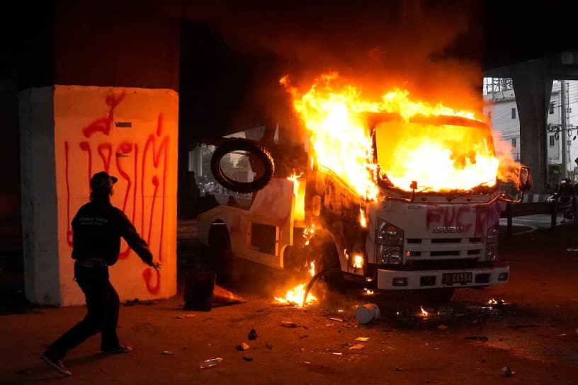 Бангкок, Таиланд. Демонстрант бросает шины в горящий полицейский грузовик во время антиправительственной акции протеста