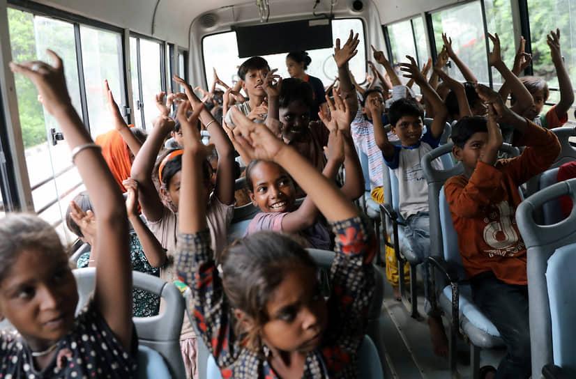 Нью-Дели, Индия. Дети хлопают в ладоши в припаркованном автобусе, который используется в качестве мобильного класса для детей, живущих в трущобах