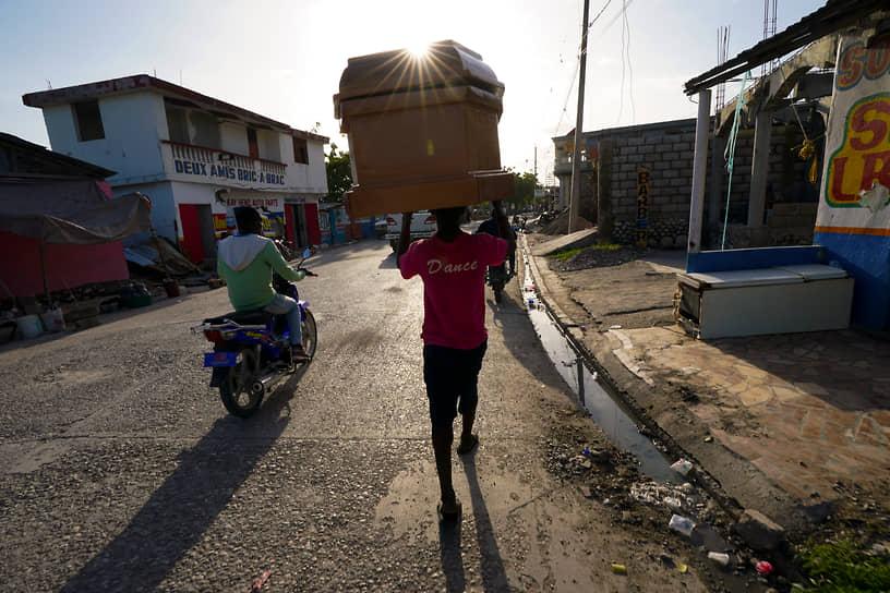 Ле-Ке, Гаити. Рабочий несет гроб в похоронное бюро после землетрясения магнитудой 7,2 балла