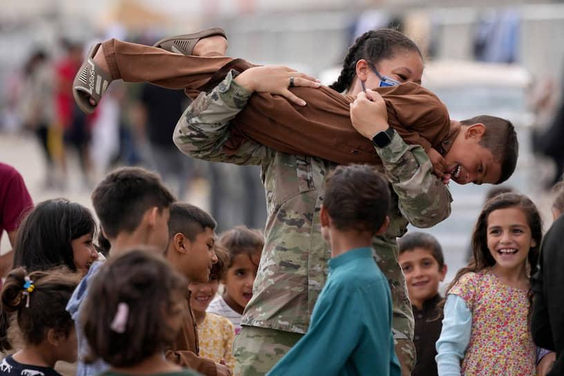 Рамштайн, Германия. Американская военнослужащая играет с детьми, эвакуированными из Афганистана