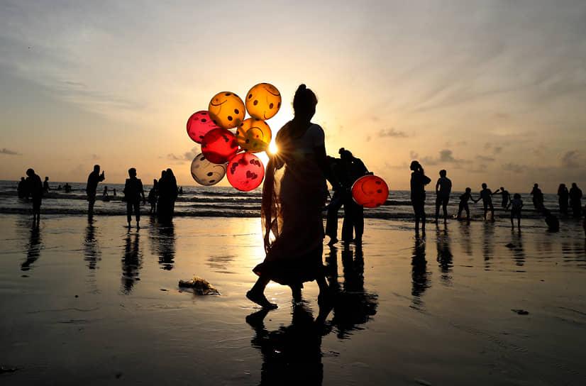 Мумбаи, Индия. Женщина продает воздушные шары на пляже