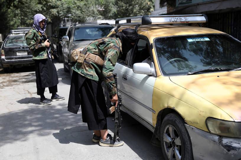Страну также пытаются покинуть и граждане Афганистана <br>На фото: боевики проверяют автомобили на контрольно-пропускном пункте