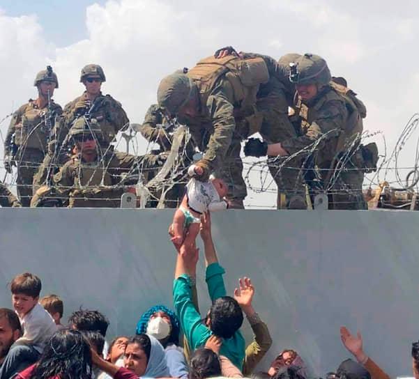 22 августа президент США Джо Байден рассказал, что с середины августа из Афганистана вывезено 28 тыс. человек, с июля — 33 тыс. <br>На фото: афганец передает американским солдатам ребенка