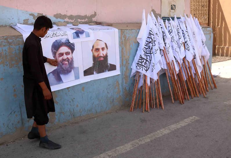 23 августа при столкновении у аэропорта Кабула погибли семь человек, в том числе четверо пытавшихся покинуть Афганистан <br>На фото: местный житель продает плакаты с изображением лидеров террористического движения «Талибан» (запрещено в РФ)