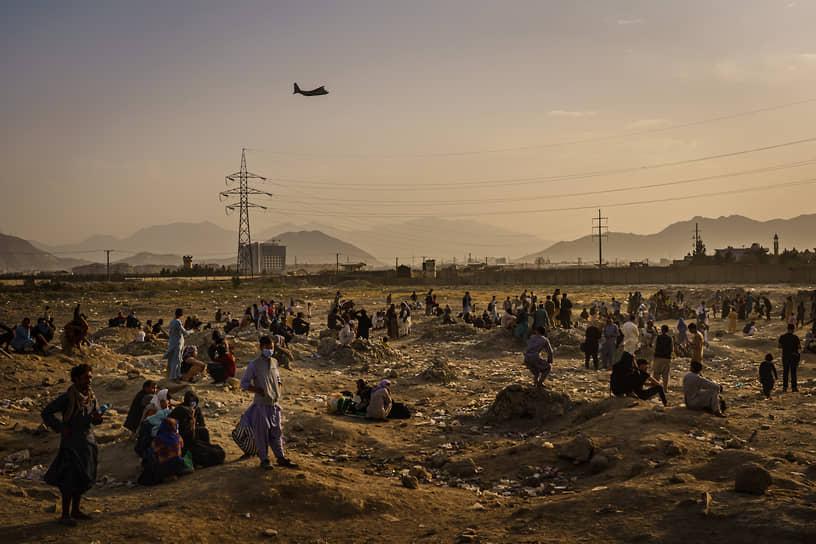 На следующий день представители террористического движения «Талибан» (запрещено в РФ) сообщили, что перекрыли дорогу, ведущую к международному аэропорту Кабула, и пропускают туда только иностранцев <br>На фото: афганцы, которые не могут попасть в аэропорт, наблюдают за пролетающим военным транспортным самолетом