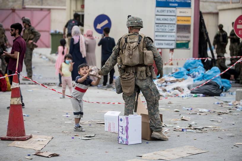 Американский морпех раздает еду в аэропорту Кабула