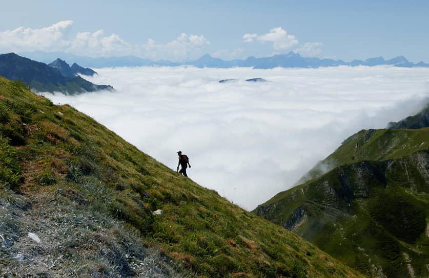 Грюйер, Швейцария. Путешественник поднимается на гору