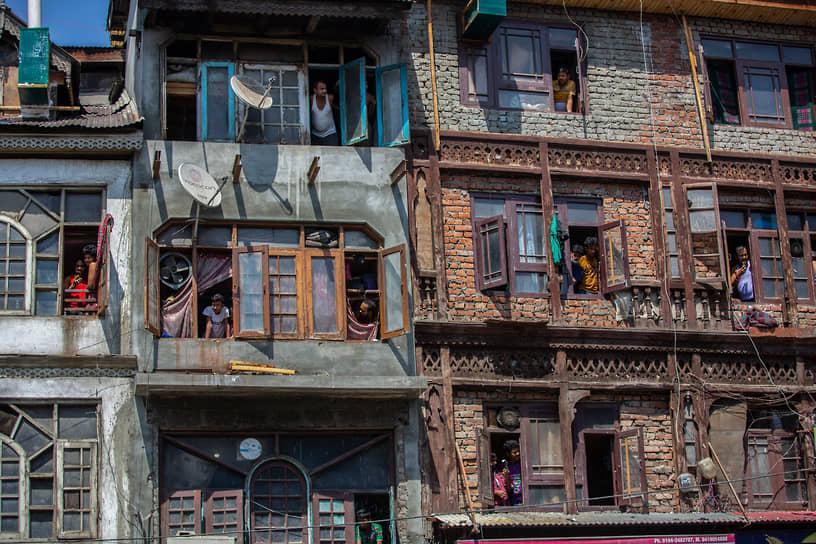 Сринагар, Индия. Люди наблюдают из окон за религиозной процессией верующих-индуистов