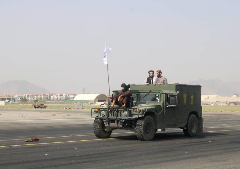 Талибы патрулируют взлетно-посадочную полосу в Кабуле на трофейном автомобиле через день после вывода американских войск