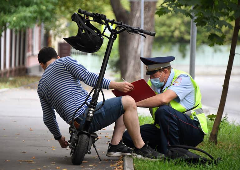 Москва. Сотрудник ДПС во время оформления протокола с водителем электросамоката