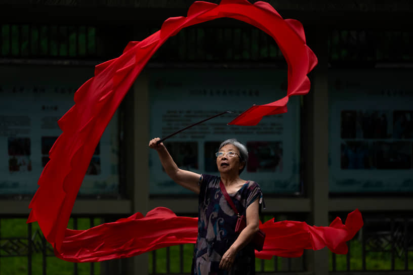 Пекин, Китай. Женщина занимается упражнением в парке