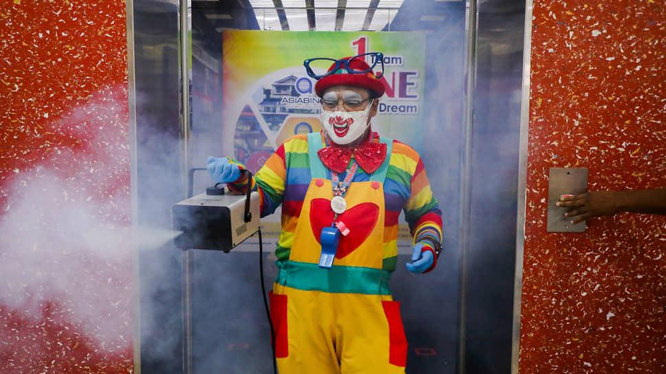 Тайпин, Малайзия. Мужчина в костюме клоуна дезинфицирует лифт в торговом центре