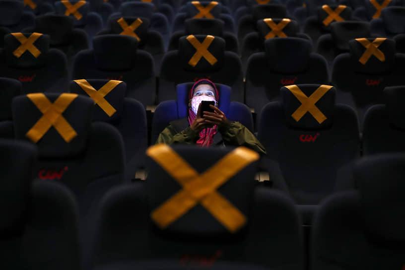 Джакарта, Индонезия. Зритель в зале в первый день открытия кинотеатров в городе после коронавирусных ограничений