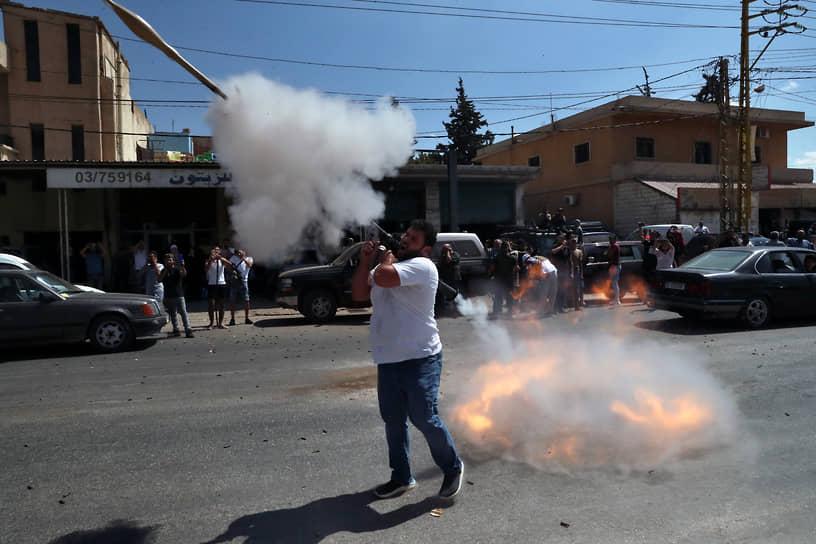 Баальбек, Ливан. Сторонник «Хезболлы» стреляет в воздух  из гранатомета в честь прибытия в страну иранских бензовозов