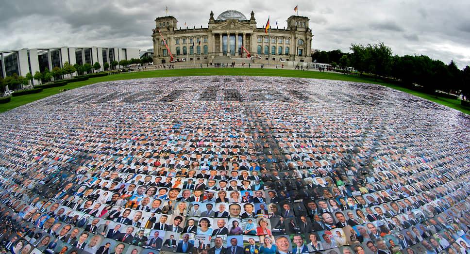 Берлин, Германия. Портреты политиков, разложенные перед зданием Рейхстага, в рамках акции против нарушений прав человека