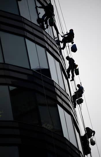 Москва, Россия. Промышленные альпинисты моют окна высотного здания