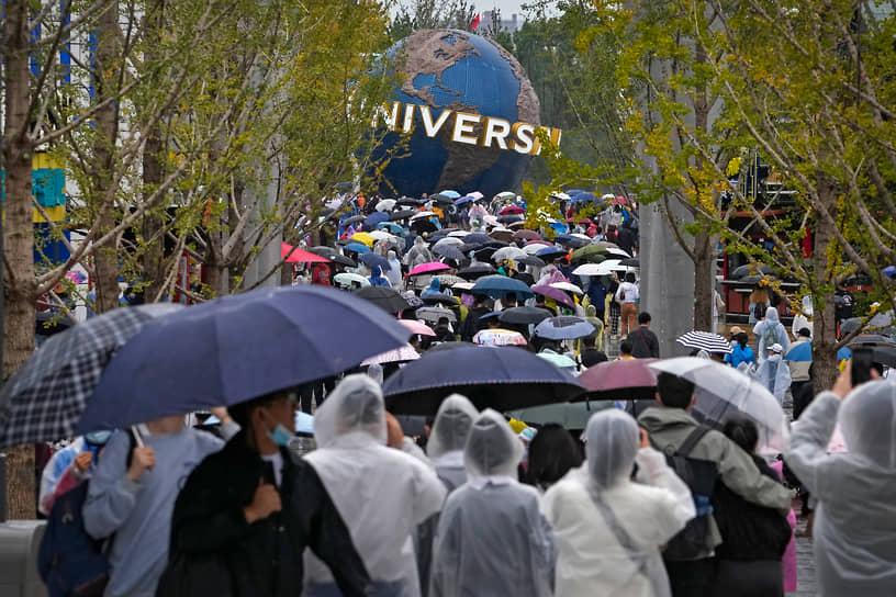 Пекин, Китай. Люди в дождевиках и с зонтами перед открытием тематического парка Universal Studios Beijing