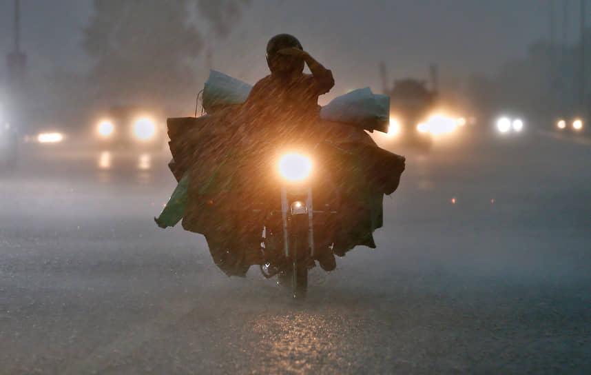 Исламабад, Пакистан. Мотоциклист едет во время ливня