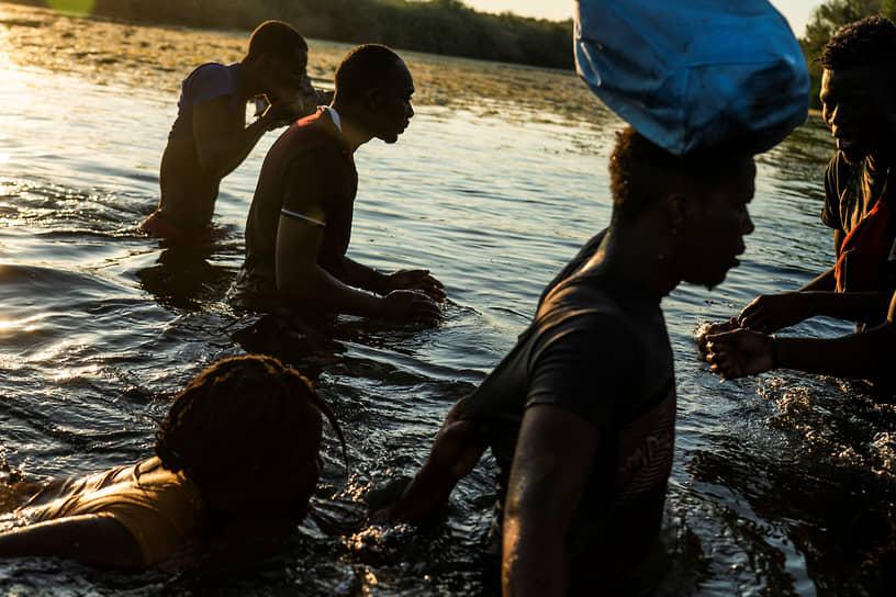 Сьюдад-Акунья, Мексика. Мигранты переходят в брод реку Рио-Гранде на границе с США