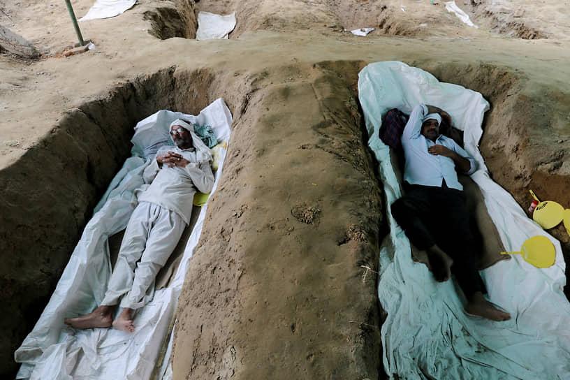 Газиабад, Индия. Фермеры лежат в выкопанных ямах на акции протеста