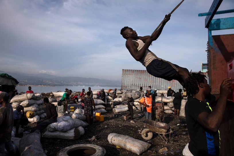Порт-о-Пренс, Гаити. Мужчина забирается на грузовик во время погрузки угля