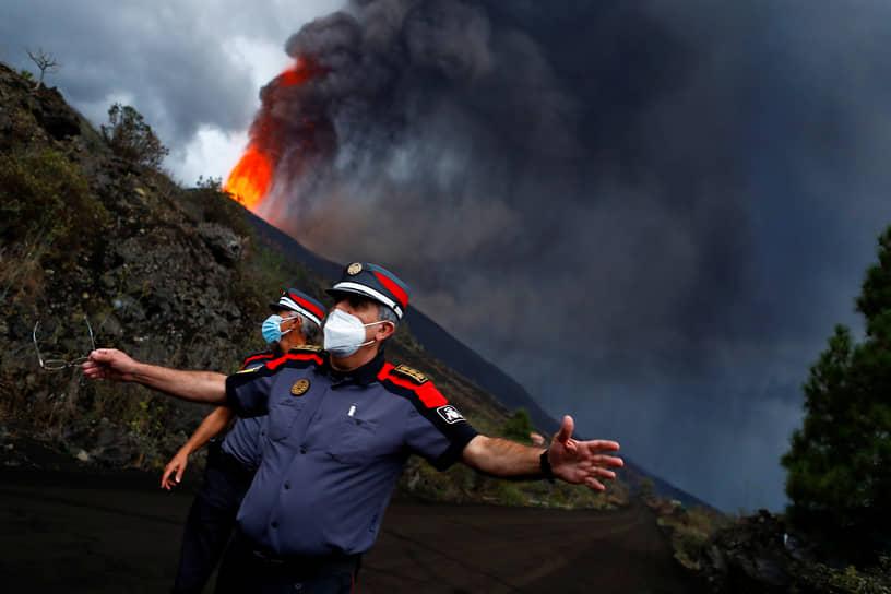 Остров Пальма, Испания. Полицейские блокируют дорогу во время извержения вулкана