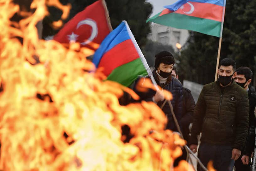 Люди с флагами Азербайджана и Турции у мемориального комплекса «Вечный огонь»