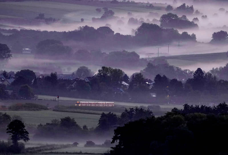 Верхайм, Германия. Поезд проезжает через туманную местность