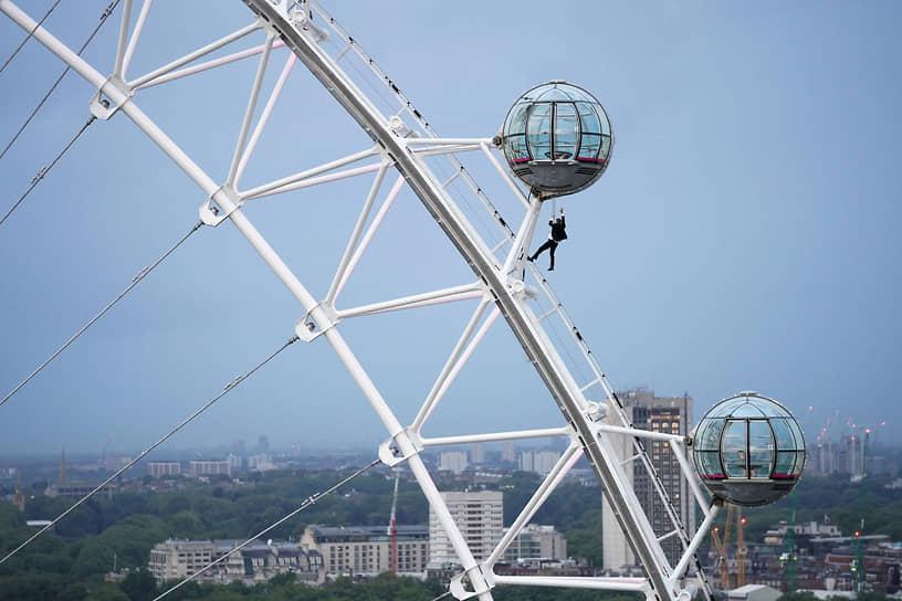 Лондон, Великобритания. Мужчина в костюме Джеймса Бонда выполняет трюк на колесе обозрения в преддверии выхода очередной части кинофраншизы об агенте 007