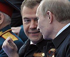 Президент России Дмитрий Медведев (слева) и председатель правительства России Владимир Путин (справа) во время проведения Военного парада на Красной площади, посвященного 66-й годовщине Победы в Великой Отечественной войне
