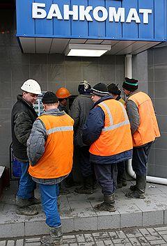 Рабочие у банкомата.  Фото: Геннадий Гуляев/Коммерсантъ.