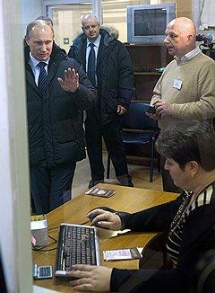 Председатель правительства России Владимир Путин (слева) и технический директор пункта технического осмотра автотранспортных средств Игорь Симаков (справа) во время посещения пункта технического осмотра автотранспортных средств в столичном районе Строгино