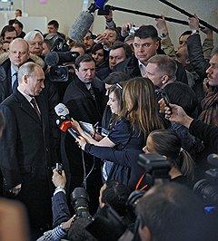 Выборы президента России. Кандидат на должность президента России, председатель правительства России Владимир Путин (слева) отвечает на вопросы журналистов после голосования на избирательном участке