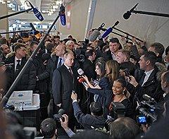 Выборы президента России. Кандидат на должность президента России, председатель правительства России Владимир Путин (в центре) отвечает на вопросы журналистов после голосования на избирательном участке