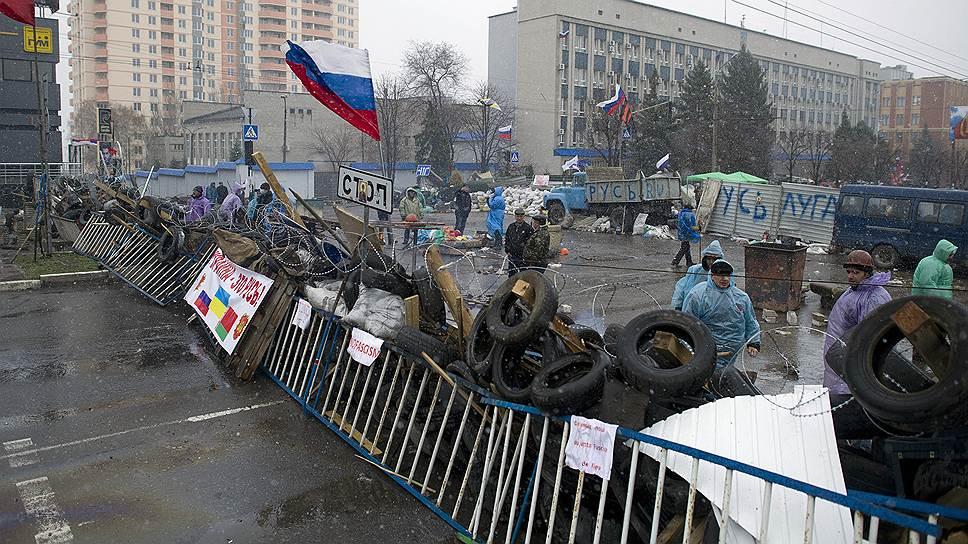 Митингующие в восточных регионах Украины, несмотря на обещания Киева, не спешат покидать захваченные ими помещения (на фото — баррикады у здания СБУ в Луганске)