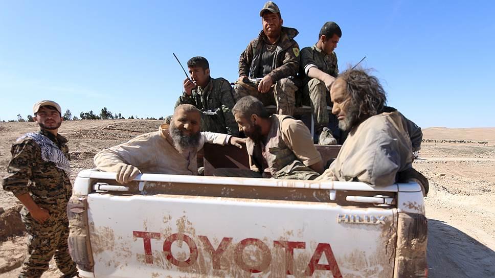 Масштабное наступление на «Исламское государство» (на фото: бойцы Демократических сил Сирии и взятые ими в плен боевики) снижает популярность идеи халифата