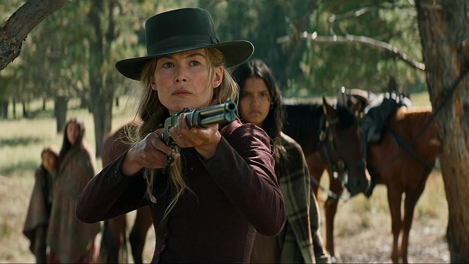 Розамунд Пайк досталась роль дамы в беде, при случае способной схватиться за ружье
