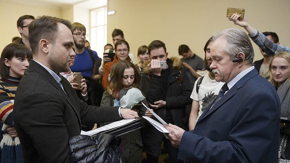 Активист инициативной группы Александр Замятин (слева) безуспешно пытался передать петицию на имя ректора МГУ его заместителю Петру Вржещу (справа)