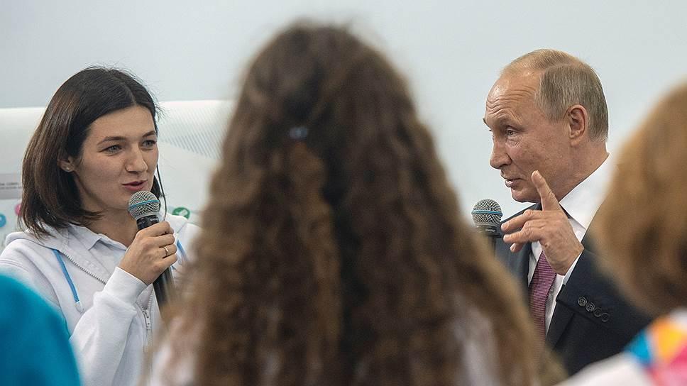 На встрече с волонтерами Владимир Путин что-то недоговаривал, а слова за его спиной кто-то, казалось, недописывал, но получалось от этого еще лучше