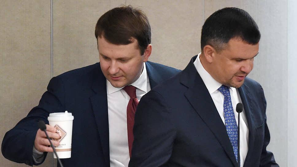Представители правительства (слева — глава Минэкономики Максим Орешкин, справа — вице-премьер Максим Акимов) на слушаниях в Госдуме признали, что подготовка законопроектов по регулированию «цифры» «проходит тяжело»