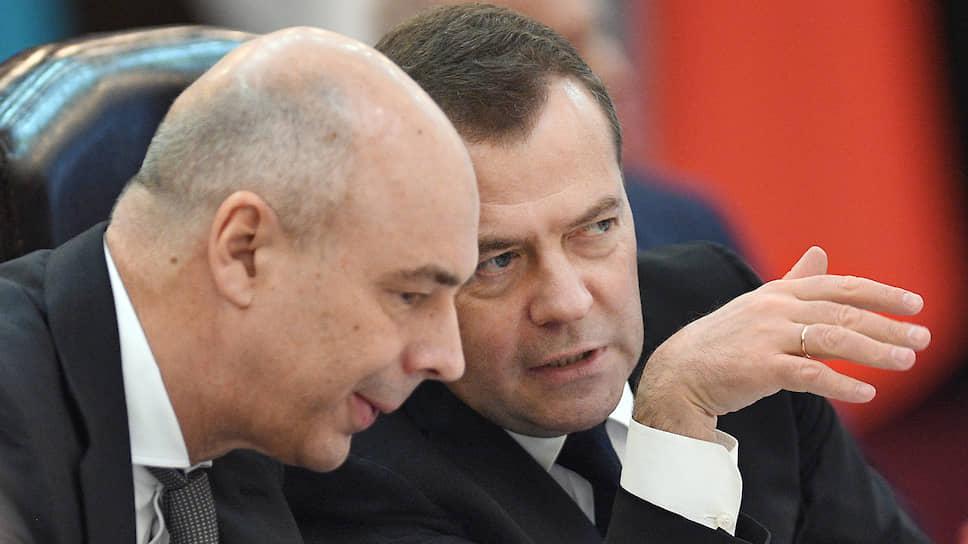 Возглавляемый Антоном Силуановым (слева) Минфин доложил главе правительства Дмитрию Медведеву, что время для включения трех из шести неналоговых платежей в НК еще не пришло